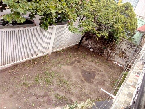 Jardín descuidado, sin pasto. Dos arbustos y un árbol de guanábanas o guanábano.